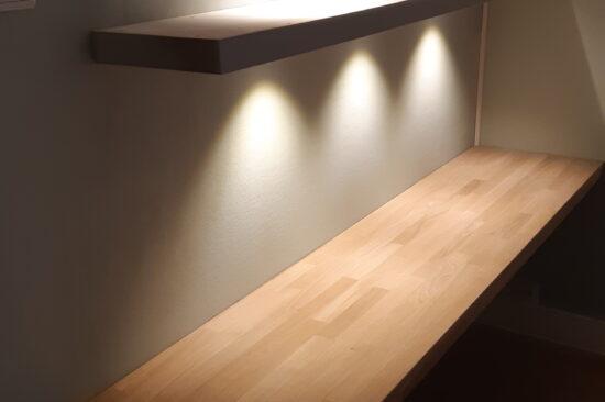 Eiken bureau met zwevende wandplanken met LED spots.